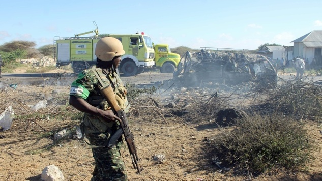 An AMISOM soldier stands guard close to destroyed vehicles following a suicide attack which targeted a convoy of African Union troops on September 8, 2014. (Photo/AFP).
