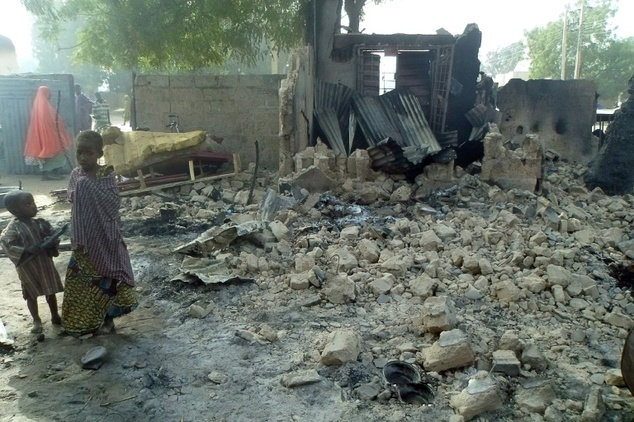 Children stand near the rubble of a burnt house after Boko Haram attacks at Dalori village on the outskirts of Maiduguri in northeastern Nigeria on January 31, 2016