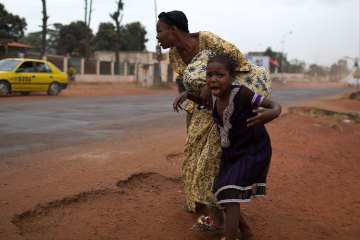 A mother holds her child while attempting to take cover as repeated gun shots are heard close to Miskine district during continuing sectarian violence in the capital Bangui, Jan. 28, 2014.  Read more: Central African Republic: U.N., E.U. Plot Peacekeeping Reinforcements | TIME.com http://world.time.com/2014/01/30/can-peacekeepers-save-the-central-african-republic/#ixzz2tPfvWbOm